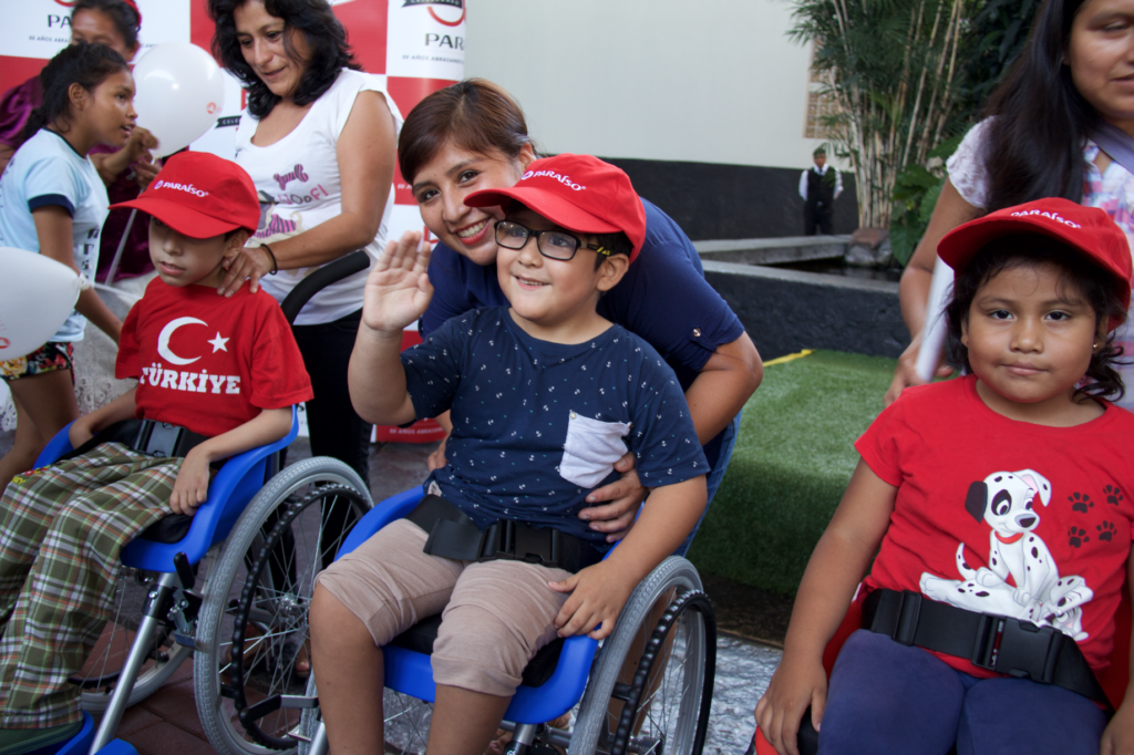 Child waves in wheelchair of hope