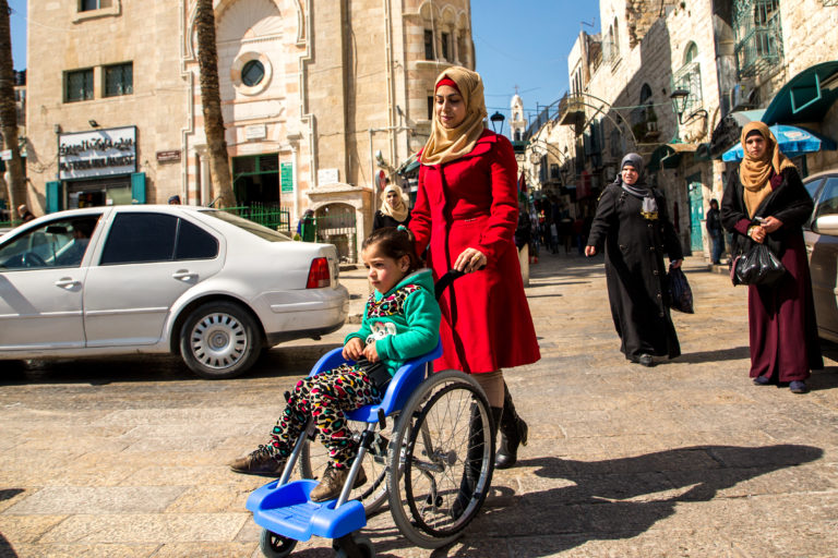 Mother wheels child in wheelchair of hope