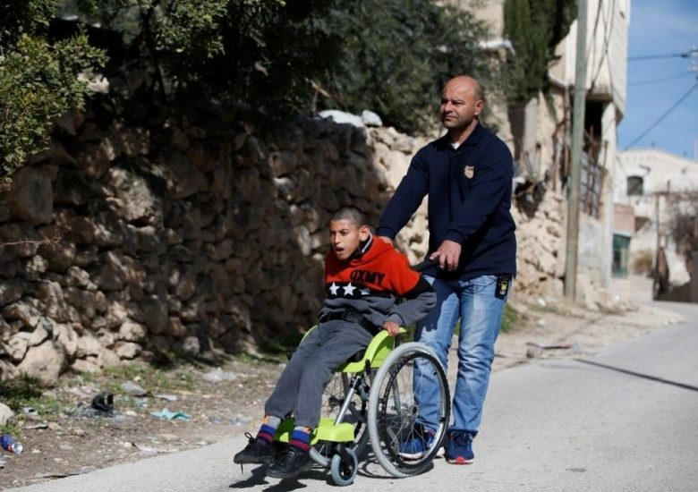 Father wheels child in wheelchair of hope