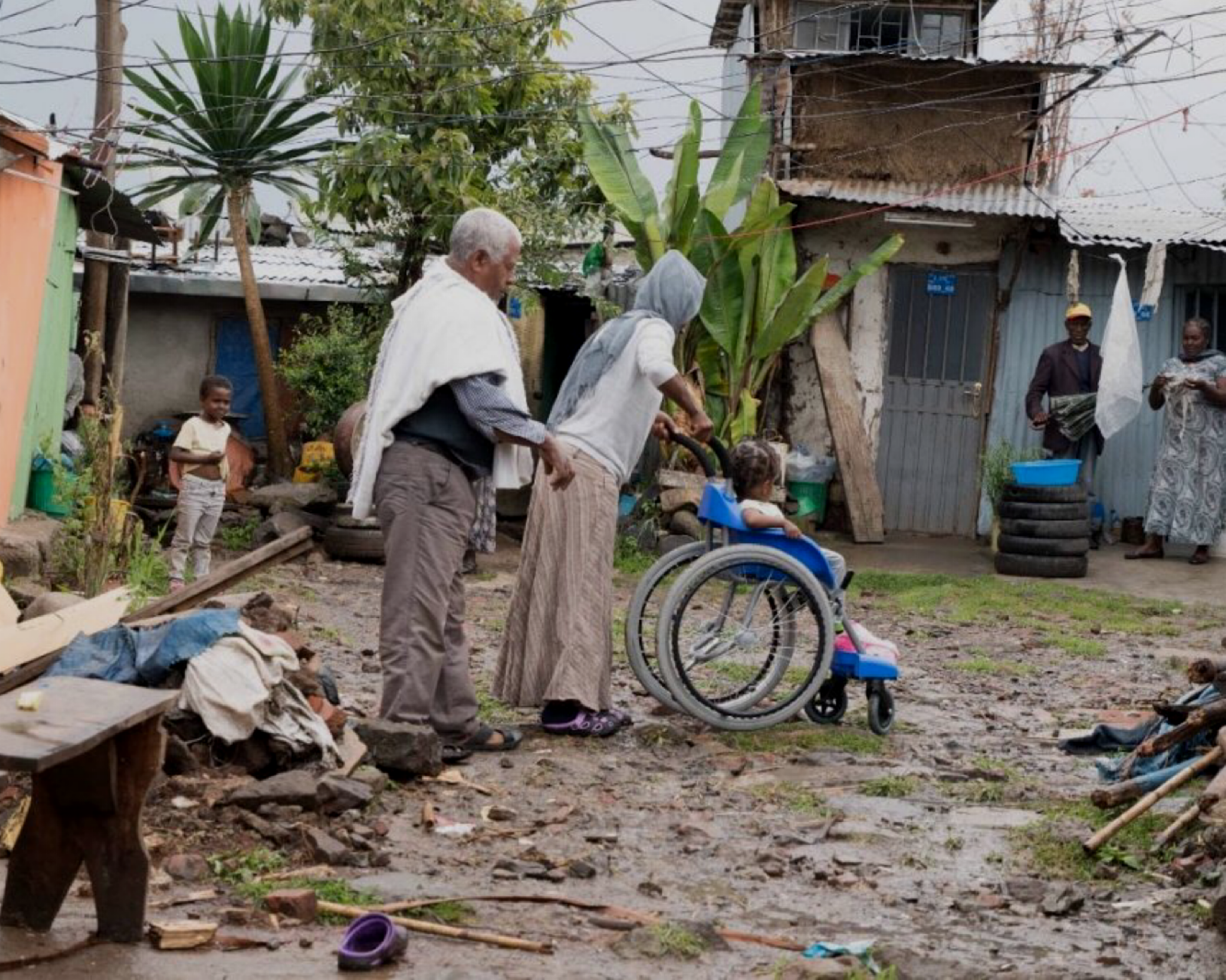 parents pushing child in wheelchair through the mud
